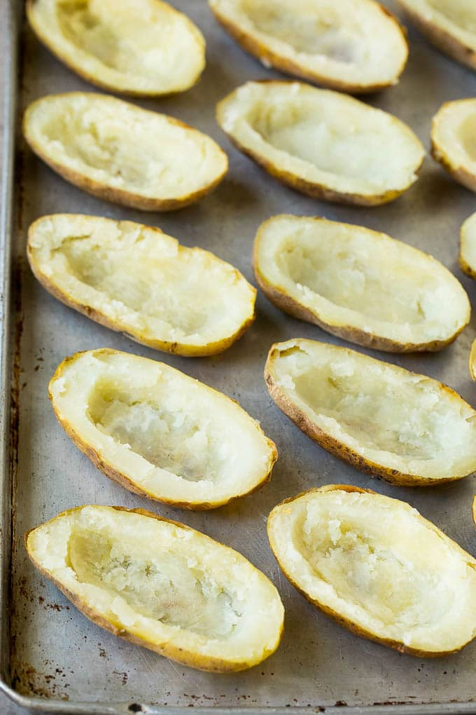 Hollowed out potato halves on a sheet pan.