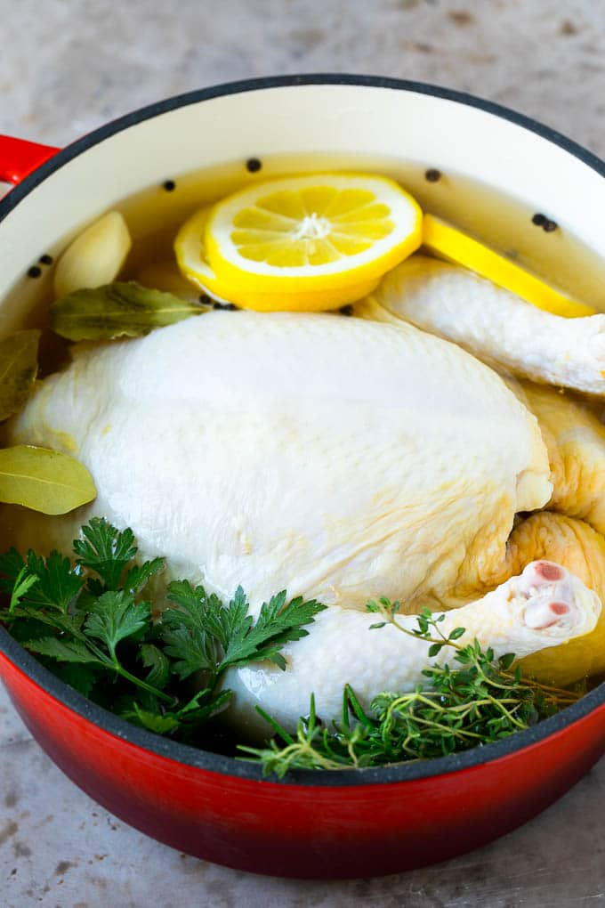 A whole chicken in a pot of brine.