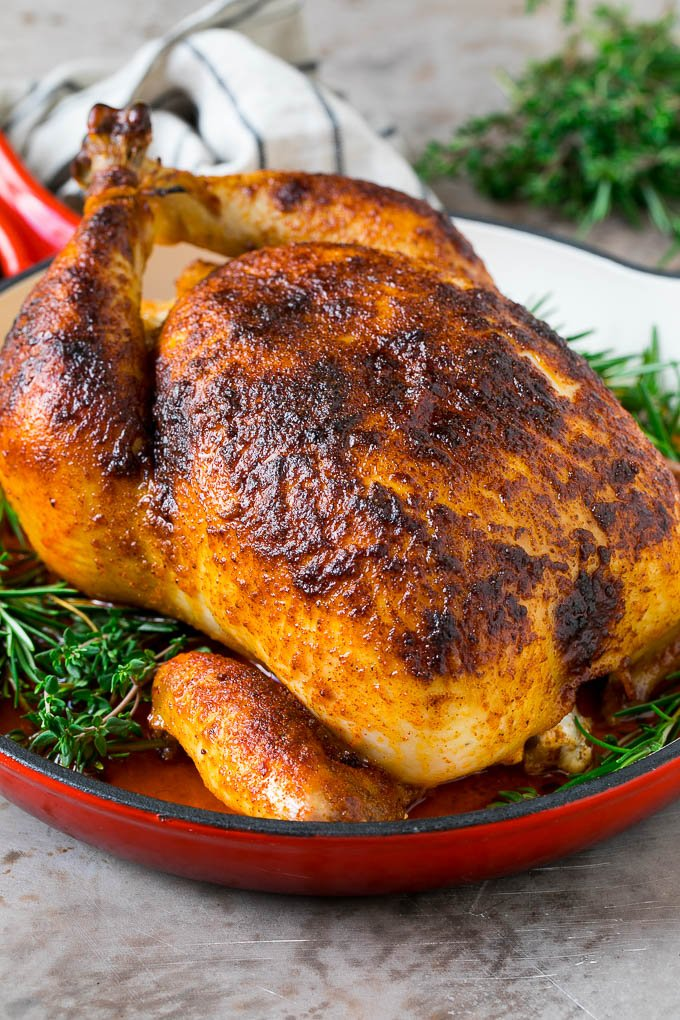 Rotisserie chicken in a skillet garnished with fresh herbs.