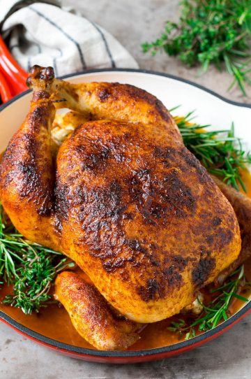 A rotisserie chicken in a red skillet with sprigs of fresh herbs.
