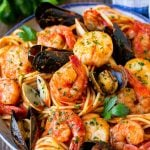 A bowl of seafood pasta with shrimp, clams and scallops.