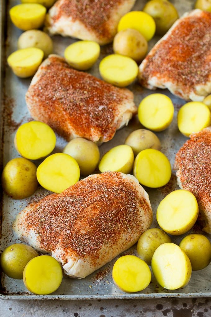 Chicken thighs coated in spices with small potatoes.