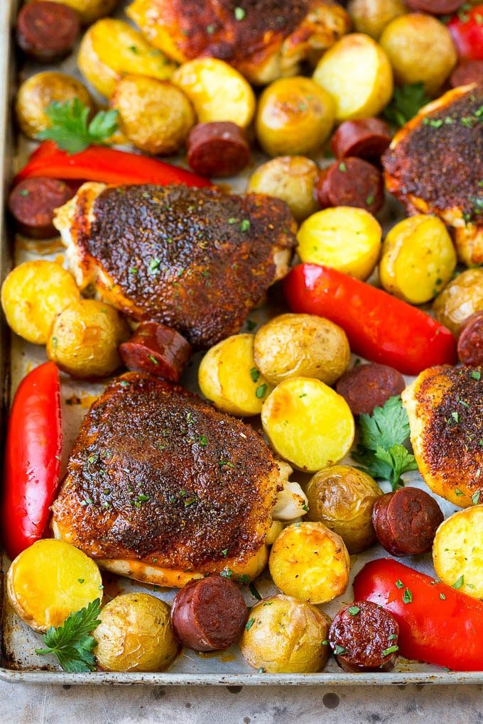 A sheet pan of Spanish chicken with potatoes, bell peppers and sausage.