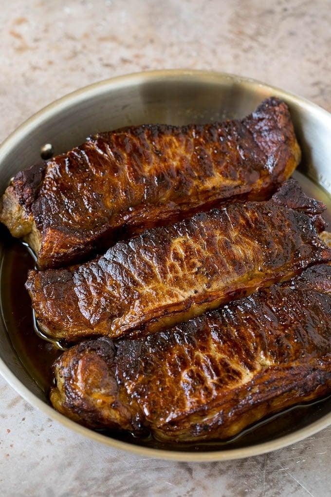 Seared strip steaks in a skillet.