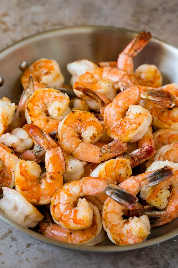 Sauteed jumbo shrimp in a skillet.