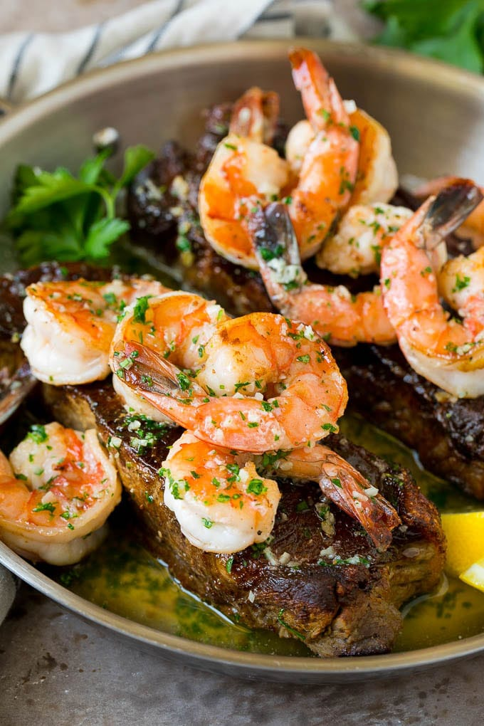 Surf and turf with seared strip steaks topped with jumbo shrimp.