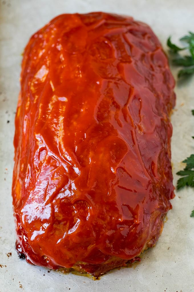 A baked meatloaf topped with ketchup.