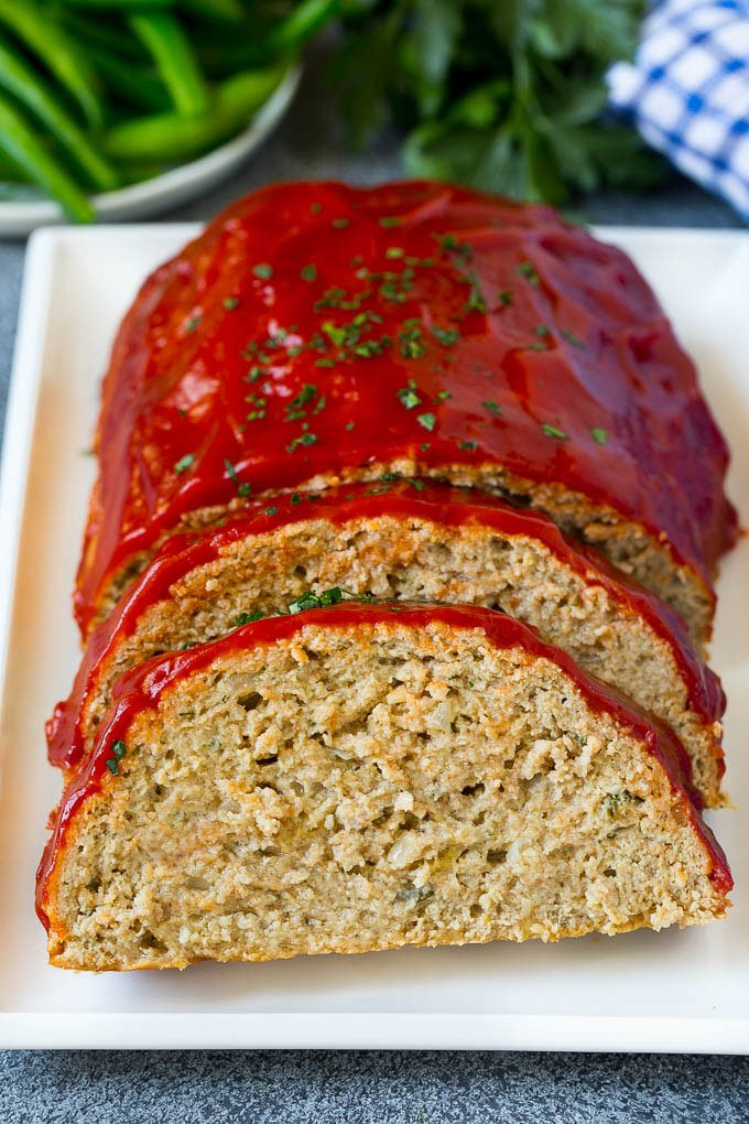 A sliced turkey meatloaf topped with ketchup and chopped parsley.