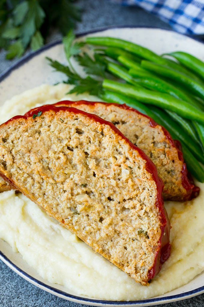 Sliced turkey meatloaf served over mashed potatoes with green beans.