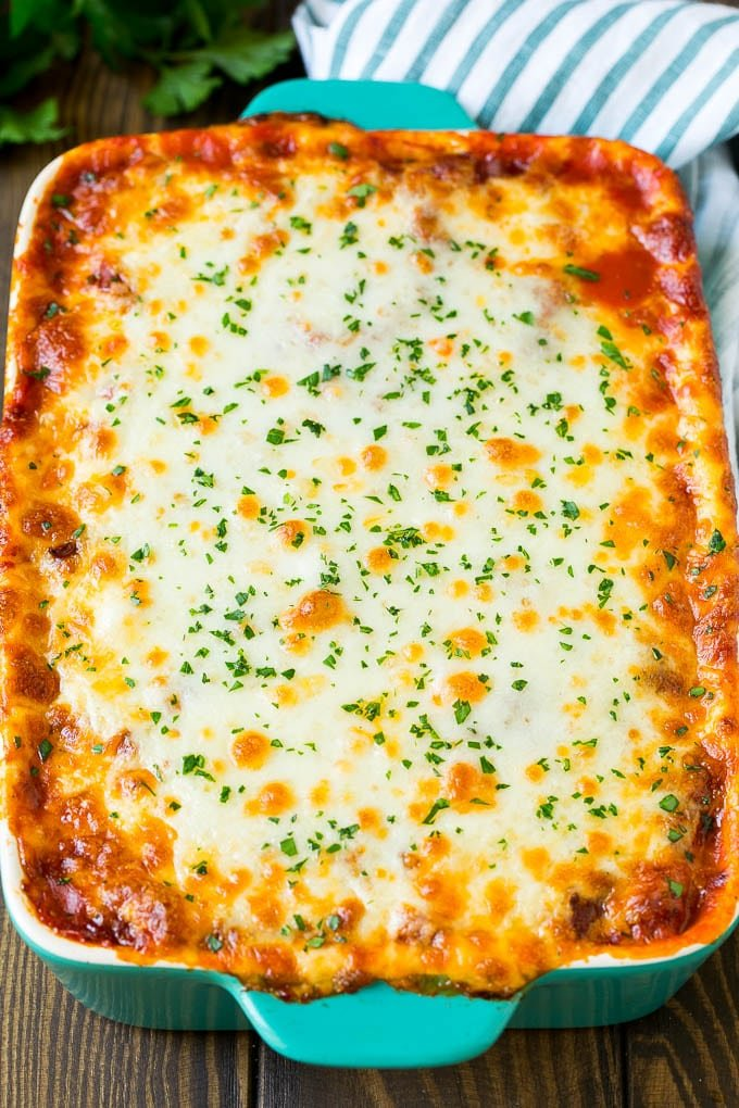 A baked zucchini lasagna topped with melted cheese and parsley.