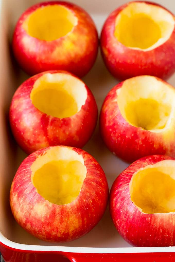 Hollowed out apples in a baking dish.