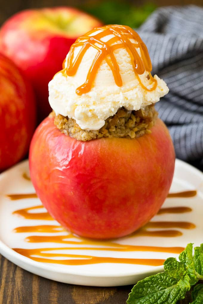 A baked apple topped with vanilla ice cream and caramel sauce.