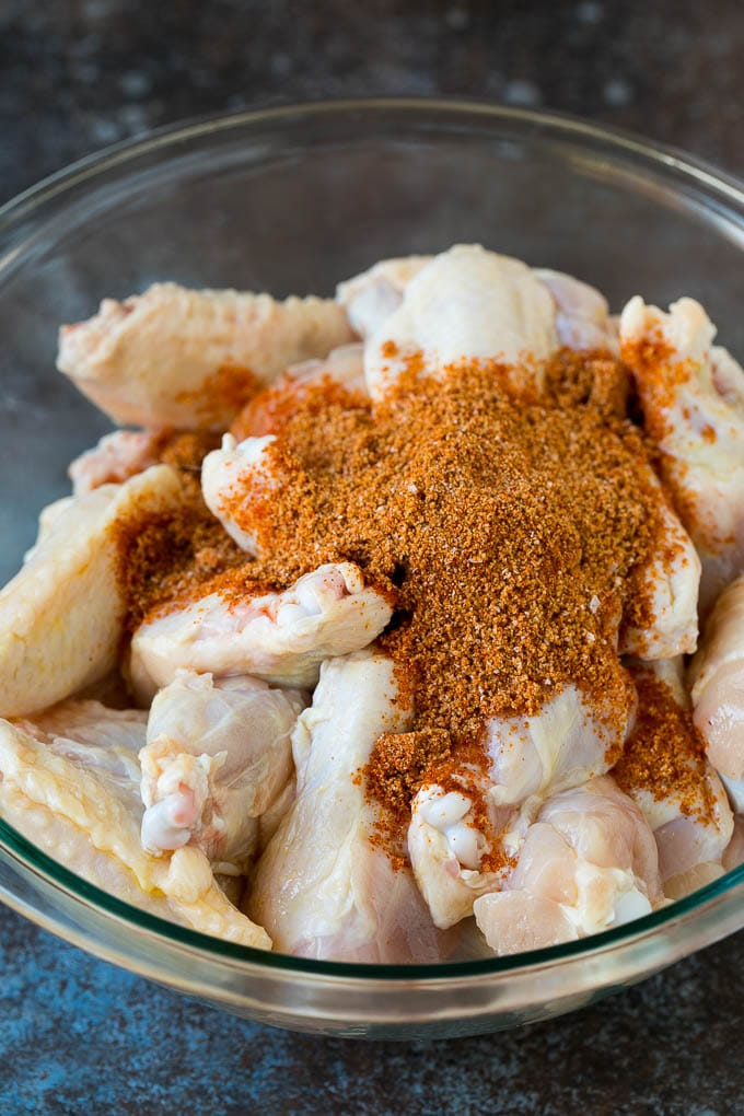 Chicken wings and spice rub in a mixing bowl.