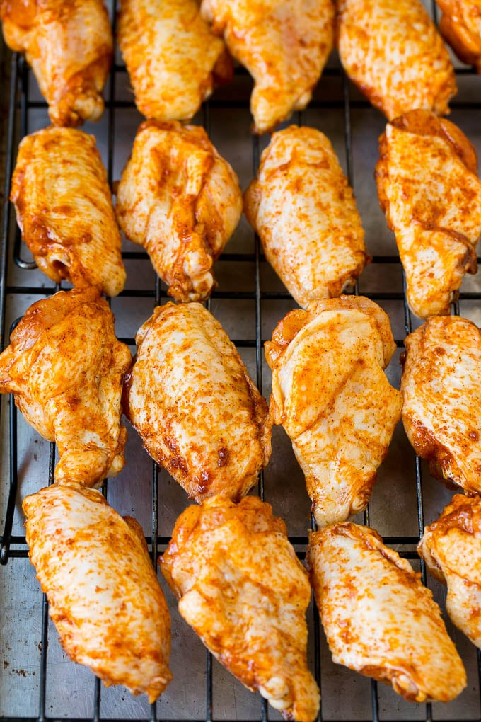 Spice coated chicken wings on a baking rack.
