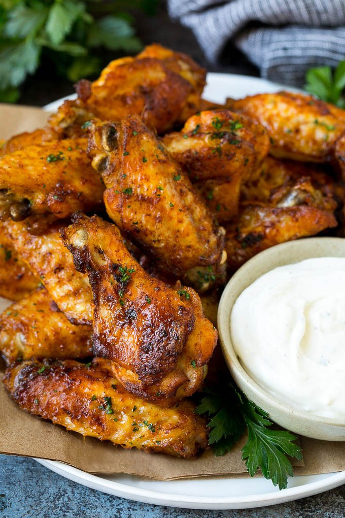 Baked chicken wings coated in spices and served with ranch dip.