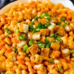 Buffalo chicken mac and cheese with crispy chicken pieces, celery and hot sauce.