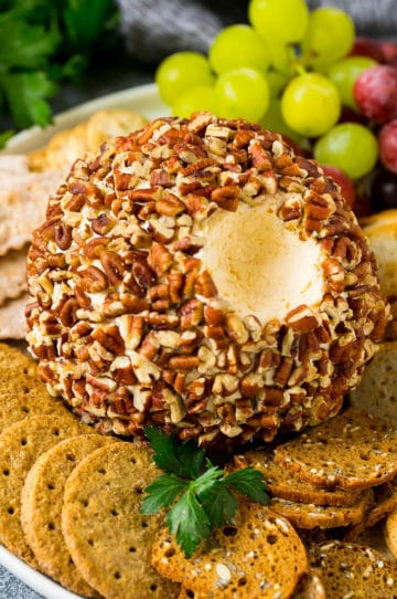 A cheese ball with a serving scooped out.