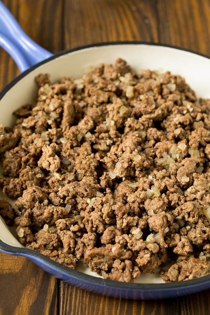 Ground beef with onions in a skillet.