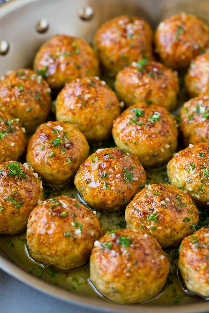 Chicken meatballs in a skillet of garlic butter.