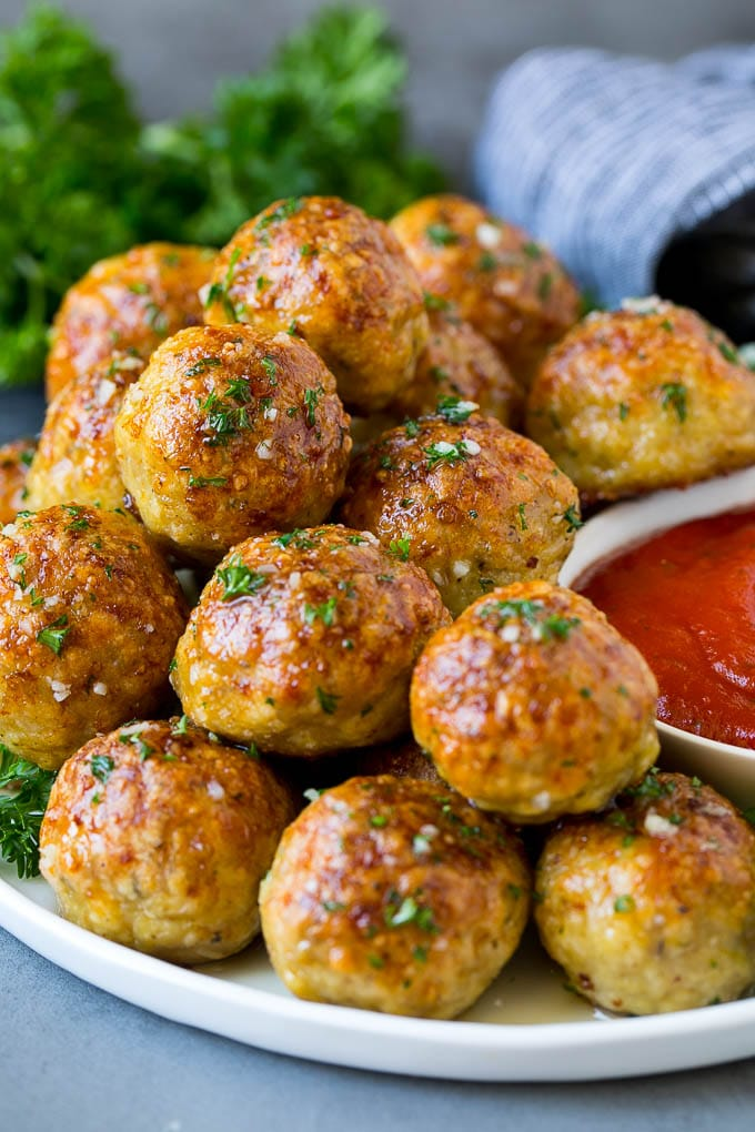 A serving plate of chicken meatballs served with marinara sauce.