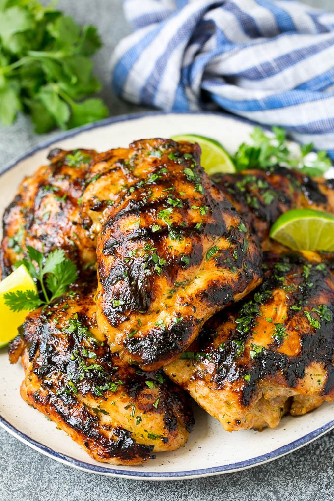 Grilled chicken thighs with a garnish of cilantro and lime wedges.