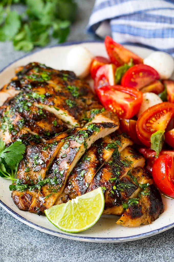 Sliced chicken thighs served with tomato salad.