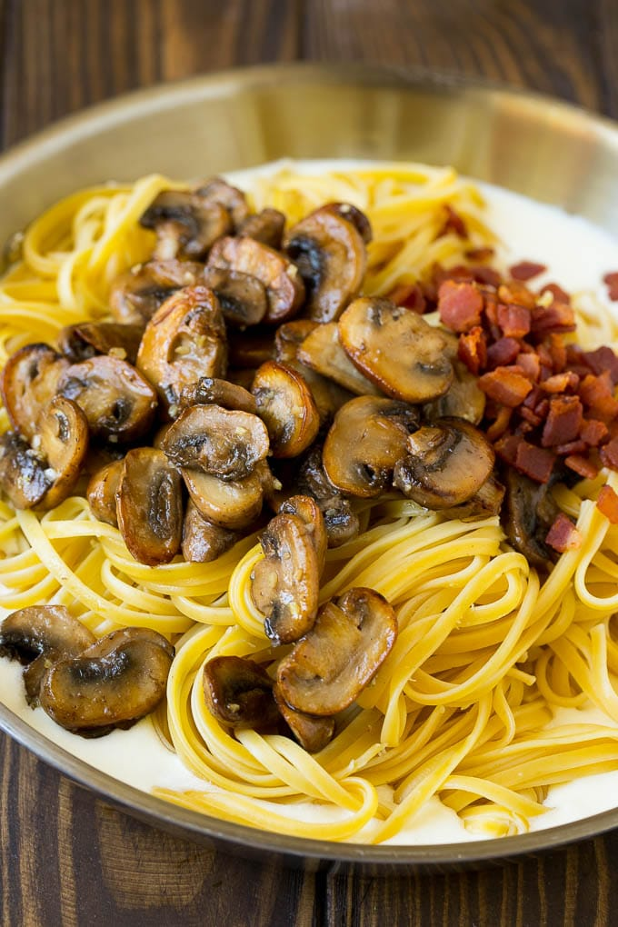 A pan of cream sauce with pasta, bacon and mushrooms.