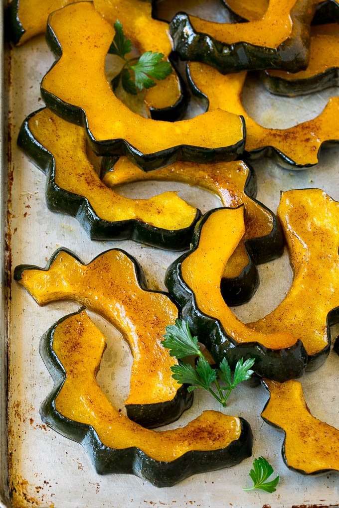 Sliced of cinnamon roasted acorn squash on a sheet pan.