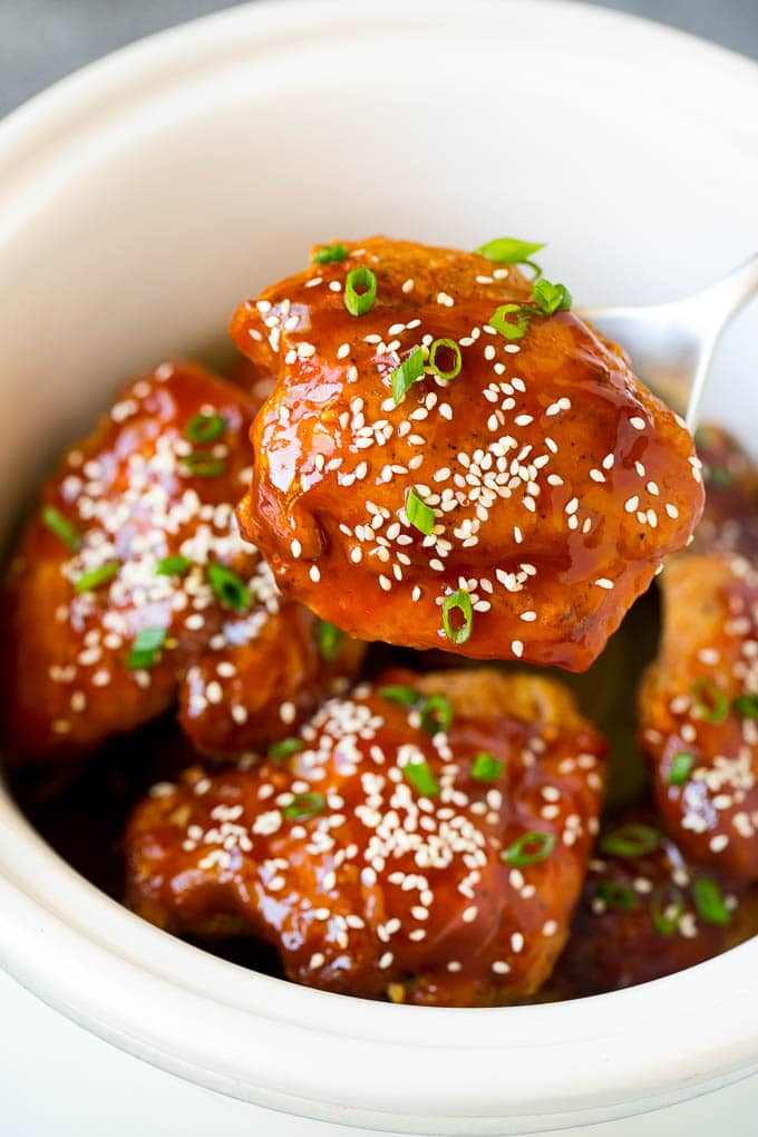 A spoon serving up a portion of honey garlic chicken.