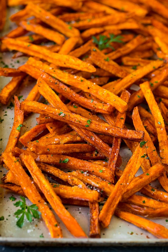 Sweet potato fries on a sheet pan, topped with salt, pepper and parsley.