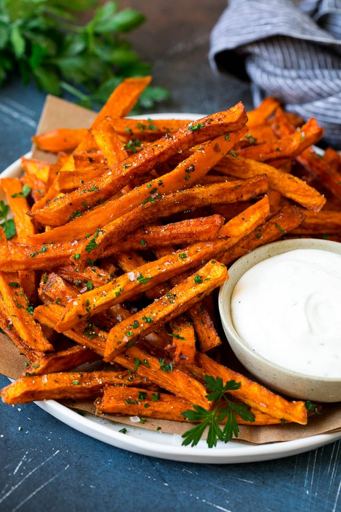 A plate of sweet potato fries with ranch dip on the side.