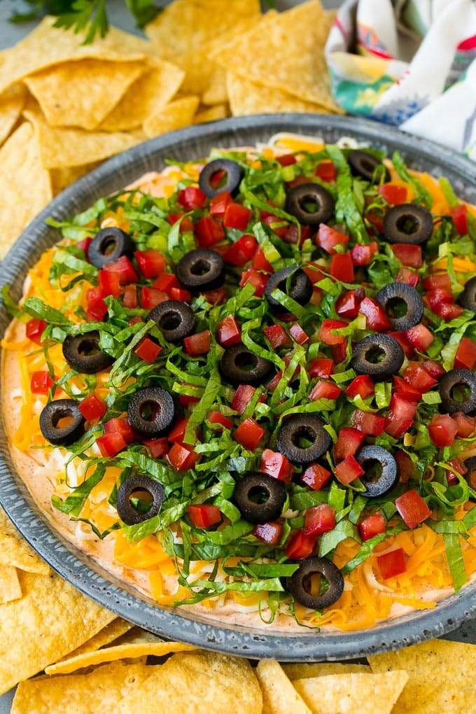 Taco dip with layers of seasoned cream cheese, lettuce, tomato, shredded cheese and olives.