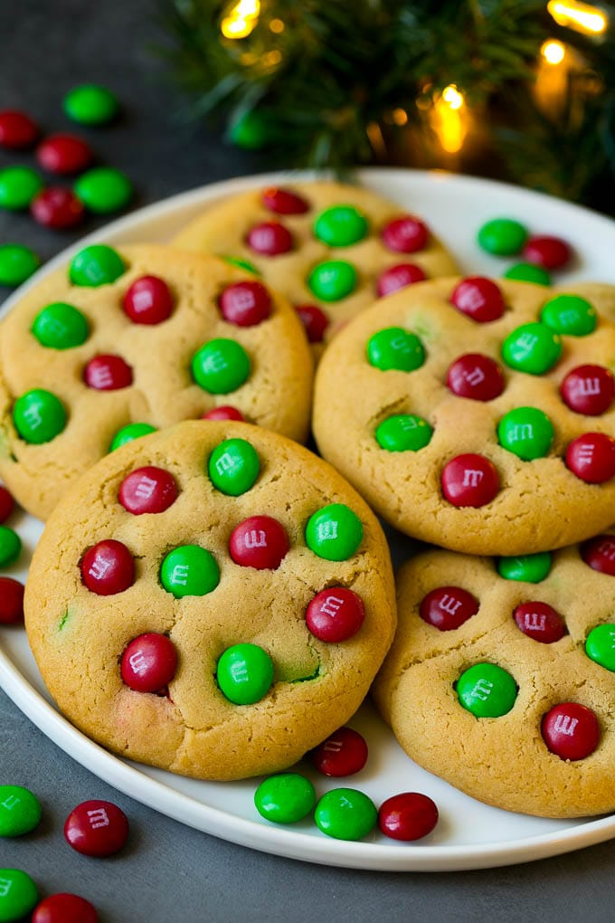 A plate of Christmas cookies with red and green M&Ms in them.
