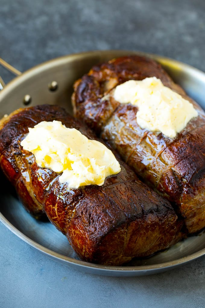 Beef roasts topped with garlic butter.