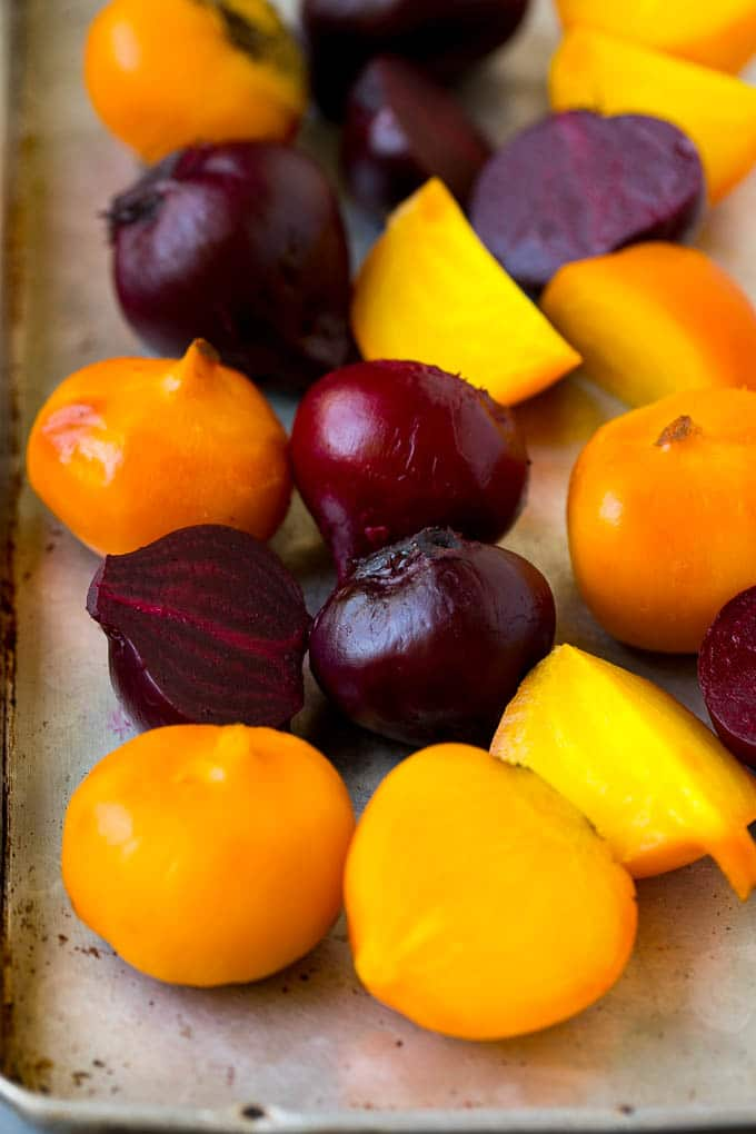 Roasted red and yellow beets on a sheet pan.