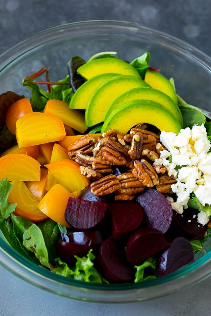 Red and yellow beets, salad greens, feta cheese, avocado and pecans in a bowl.