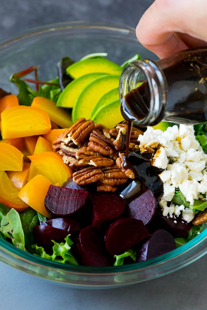 Balsamic dressing being poured over beets, sliced avocado and feta cheese.