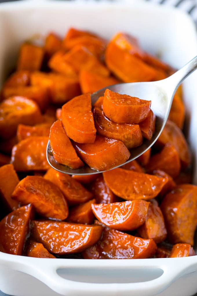 A spoon serving up a portion of candied sweet potatoes.