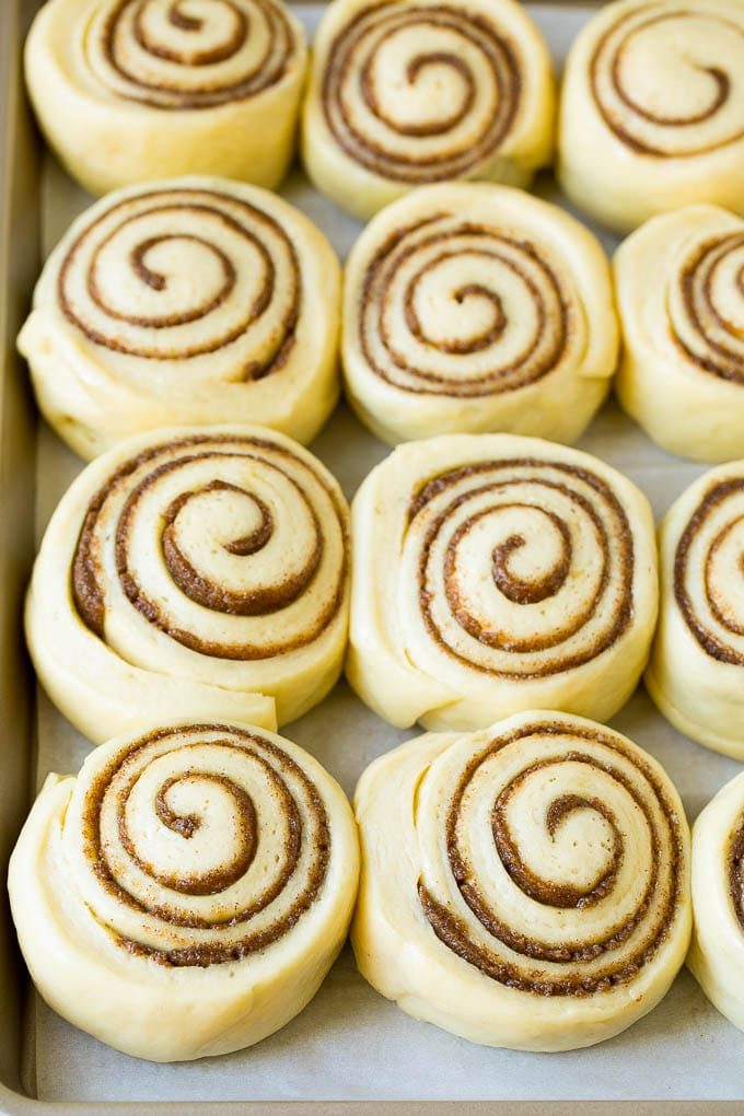 Rolls of dough and cinnamon sugar rising on a sheet pan.