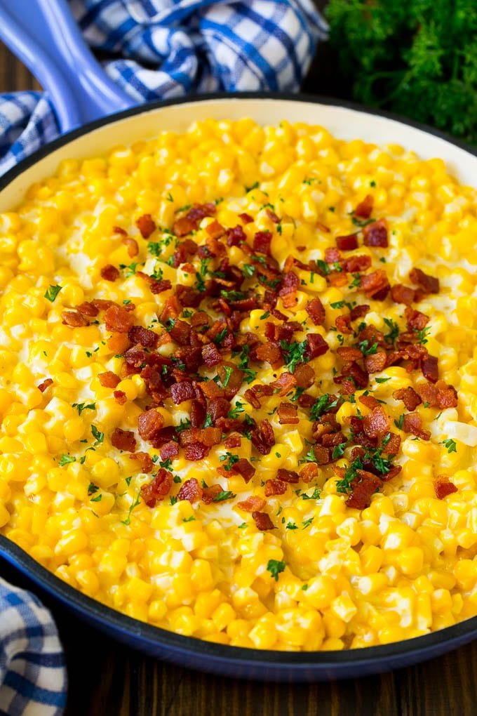 Creamed corn in a pan with bacon and parsley.