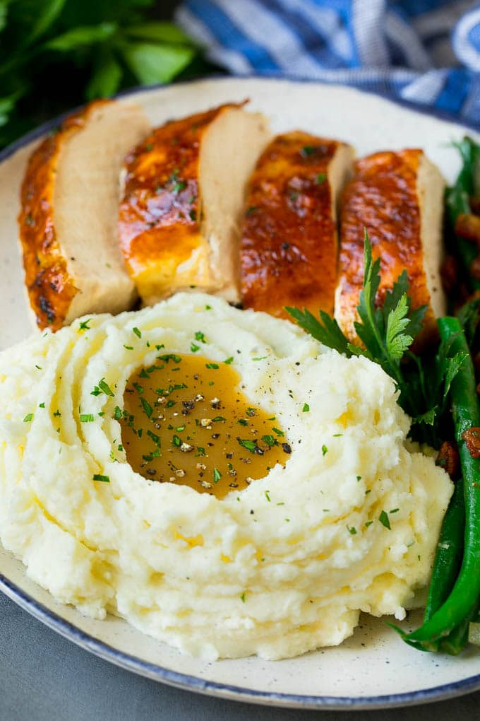 Crock pot mashed potatoes served with sliced turkey and green beans.