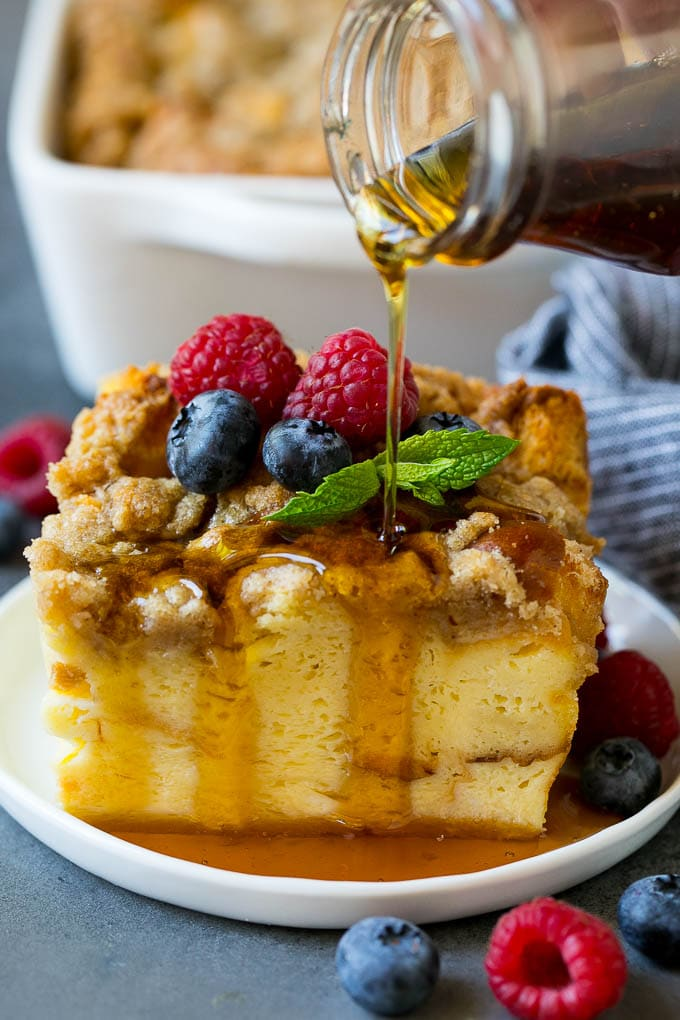 A piece of french toast casserole with syrup being poured over the top.