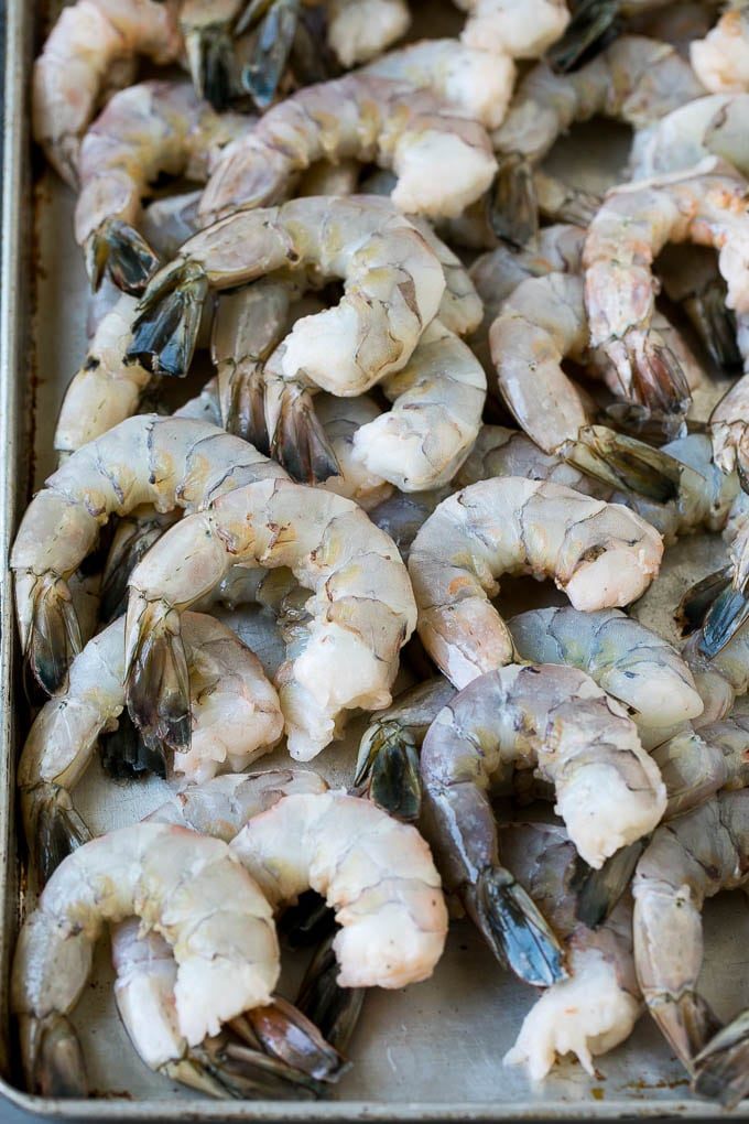 Raw shrimp on a sheet pan.