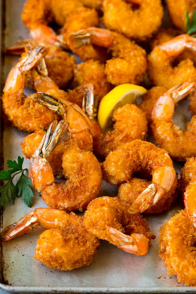 Fried shrimp on a sheet pan garnished with parsley and lemon.
