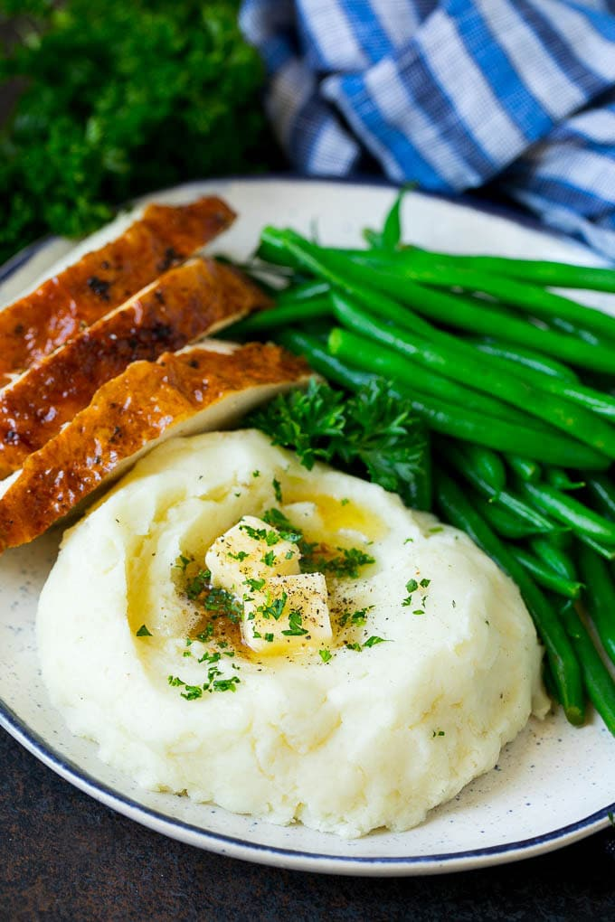 A plate with garlic mashed potatoes, green beans and sliced turkey.