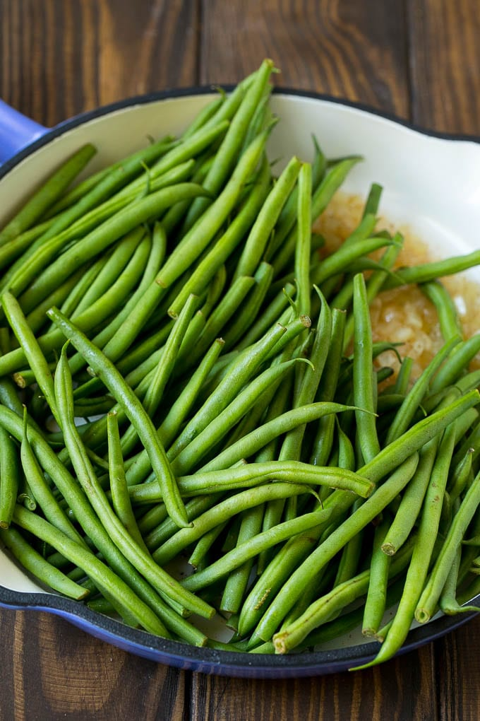 Green beans in a pan with onions.