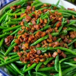 Green beans with bacon in a skillet, topped with parsley.