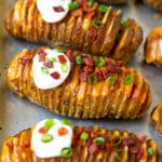 Hasselback potatoes filled with melted cheese, then topped with bacon, sour cream and green onions.