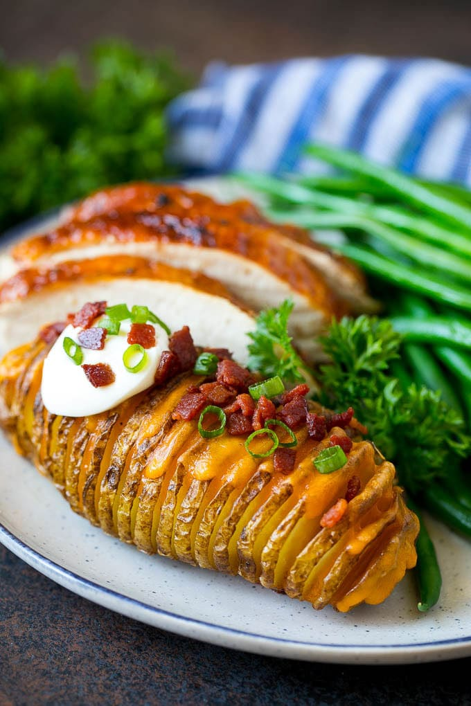 Hasselback potatoes on a plate, served with turkey and green beans.