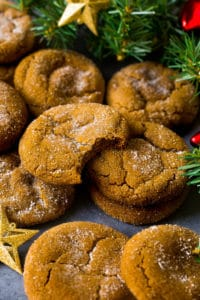 Molasses cookies coated in sugar, surrounded by holiday decorations.